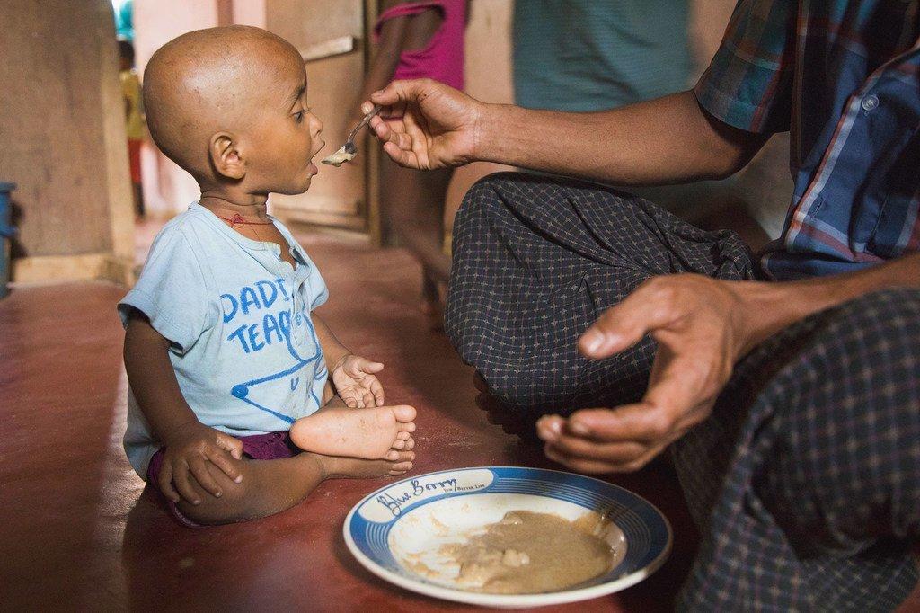 在孟加拉国的考克斯巴扎尔难民营,一个孩子正在吃饭。2019冠状病毒病可能会破坏减少饥饿的努力。