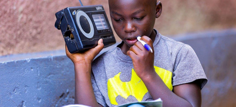 Criança no Ruanda estudando usando rádio, devido à pandemia