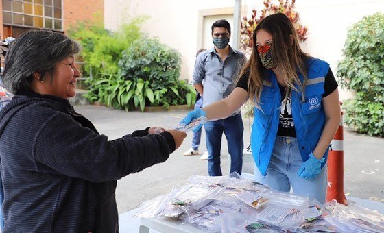 "Refugiada venezuelana recebe máscara na ""Missão Paz"", do Acnur, em São Paulo, no Brasil."