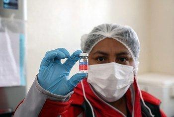 Una enfermera en un centro sanitario de Boliva sostiene una dosis de la vacuna contra la gripe.