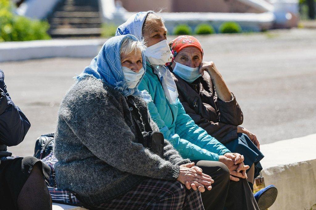 Des femmes âgées sont assises sur un mur à Hranitne,dans l'est de l'Ukraine.