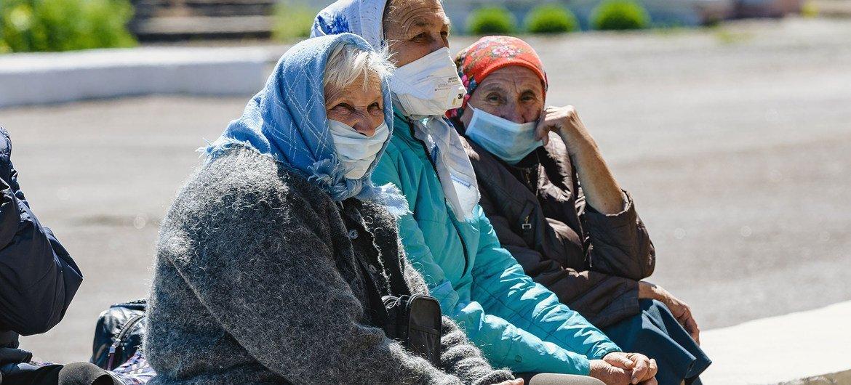 Elderly women sit on a wall in Hranitne, eastern Ukraine's frontline community.