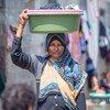 سيدة تحمل حوضا صغيرا لغسل الملابس في مخيم للنازحين في الظهير باليمن.