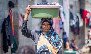Une femme porte un bol avec des vêtements lavés dans un camp de personnes déplacées dans le district d'Al-Dhihar, au Yémen.