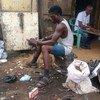 Joven trabajador de los vertederos de desechos electrónico en Ghana desensambla un aparato para obtener los materiales vaiosos.