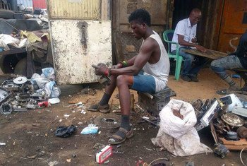 An e-waste worker disassembles items in Ghana.