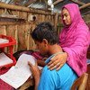 A boy studies at home while his mother sits by his side in Jessore, Bangladesh..