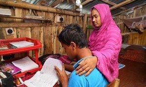 孟加拉国杰索尔一名男孩在家学习,母亲坐在他身边。
