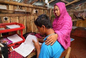 Menino estuda em casa com ajuda da mãe em Jessore, Bangladesh