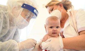 Un bebé recibe una vacuna en Kosovo durante la pandemia de COVID-19.