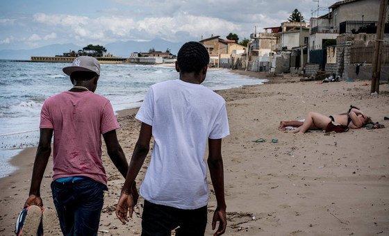 Dois irmãos adolescentes da Gâmbia que viajaram sem os pais pelo mar Mediterrâneo caminham por uma praia na Itália.