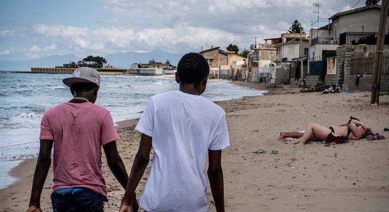 Dos menores de Gambia que cruzaron el Mediterráneo sin sus padres caminan en una playa de Italia.