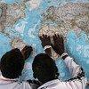 गाम्बिया के दो युवक इटली पहुंचने के बाद एक नक्शे को देखते हुए.