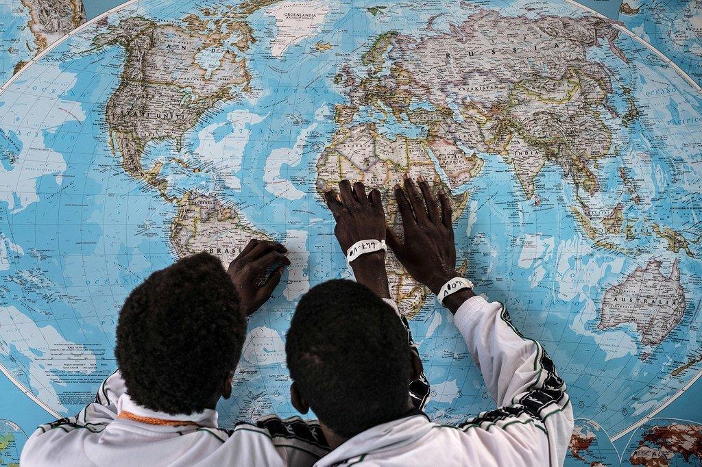 Deux jeunes migrants gambiens regardent une carte du monde après être arrivés en Italie en 2016 non accompagnés de leurs parents. (archive)