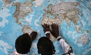 Two young  unaccompanied Gambian migrants look at a map after crossing to Italy. (file)