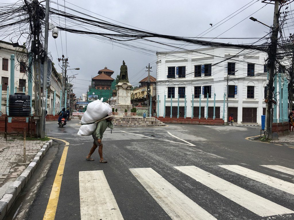 尼泊尔加德满都一个繁忙的商业区,一名男子背着沉重的包裹。新冠大流行及其相关的限制措施给人们带来了沉重的打击,许多依赖日薪的人失去了唯一的收入来源。