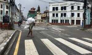 A man, carrying a load on his back, in what is generally a busy business district in Kathmandu, Nepal. COVID-19 and the associated lockdown has hit people hard, with many daily-wage earners losing their only source of income.