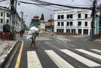 Un homme, portant une charge sur le dos, dans ce qui d'habitude un quartier d'affaires animé de Katmandou, au Népal. La Covid-19 et le confinement ont durement frappé les gens, de nombreux travailleurs journaliers ont perdu leur seule source de revenus.