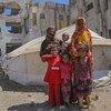 أسرة تقف أمام الخيمة التي يعيشون بها في أحد مخيمات محافظة الضالع للنازحين داخليا.