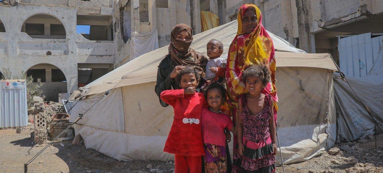 一家也门人站在一个流离失所者营地的帐篷外。