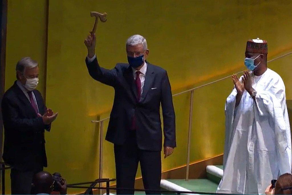 Photo ONU Web TV: Volkan Bozkir, Président de la 75ème session de l'AG, lève le marteau alors que son prédécesseur Tijjani Muhammad-Bande et le SG de l'ONU, António Guterres, applaudissent.