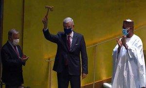 Volkan Bozkir, Président de la 75ème session de l'Assemblée générale, lève le marteau alors que son prédécesseur Tijjani Muhammad-Bande et le Secrétaire général de l'ONU, António Guterres, applaudissent.