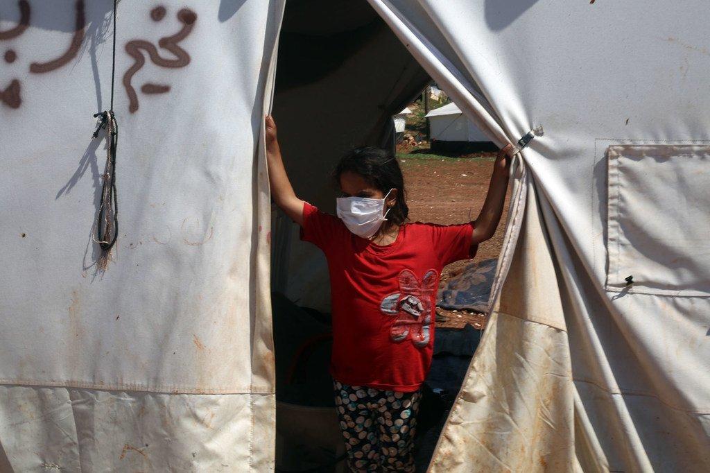 在叙利亚北部的一个营地中,一名年轻女孩戴着口罩,以免感染新冠病毒。