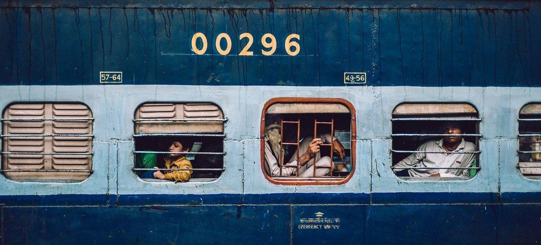 भारत की राजधानी दिल्ली में एक रेलवे स्टेशन पर पहुँचती एक रेलगाड़ी में बैठे कुछ यात्रीगण.