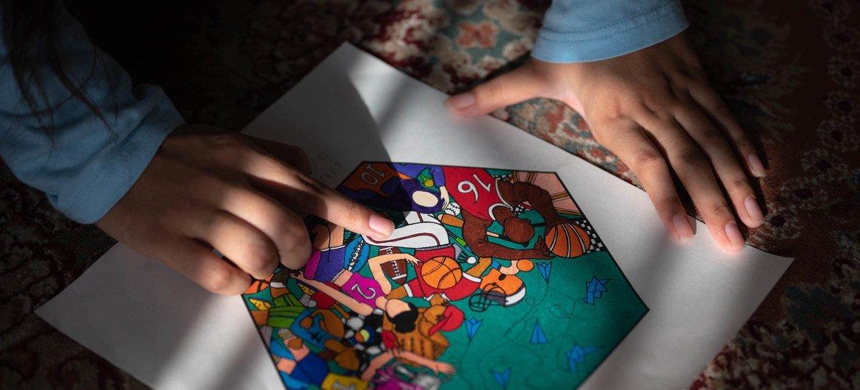 16 वर्षीय नादिरा गंजी ने, खेलों को अधिक समावेशी बनाने की आवश्यकता को उजागर करने के मक़सद से ही, फ़ुटबॉल डिज़ाइन के लिये यह चित्र कागज़ पर उकेरा था.