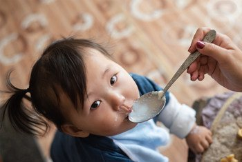 Ulaanbaatar, Mongolia - September 07, 2018: Mother giving porridge mixed with micronutrient powders (MNP) to her one-year old son in their house, in Ulaanbaatar, Mongolia. MNP aim to improve the quality of diets of nutritionally vulnerable groups, such as young children, improving complementary feeding.