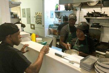 La cheffe stagiaire Roberta Mbiua (2e à gauche) reçoit ses instructions du directeur culinaire Alexander Harris au restaurant Emma's Torch à Brooklyn.