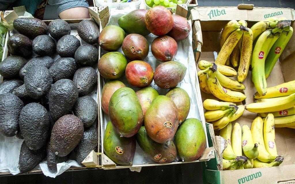Aguacates, mangos y bananas en un mercado.