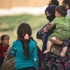 Une femme avec un enfant dans ses bras le 11 octobre 2019 en Syrie, alors que des familles déplacées arrivent à Tal Tamer, fuyant l'escalade de la violence.