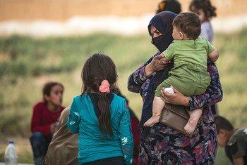 Una mujer y sus hijos llegan a Tal tamer después de ser desplazados por la guerra en el noreste de Siria.