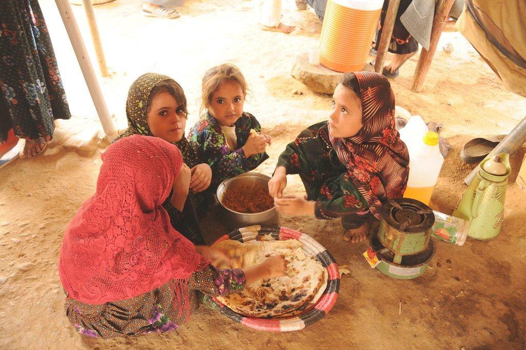 Des filles déplacées du camp d'Al-Mazraq au Yémen partagent un simple repas de pain et de légumes secs que leurs mères ont préparé (archives).