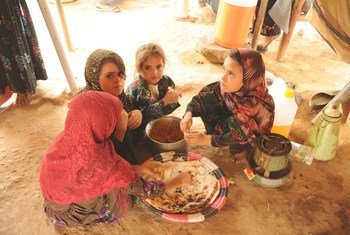 Niñas desplazadas en el campamento de Al-Mazraq en Yemen comparten una simple comida de pan y legumbres preparada por sus madres.