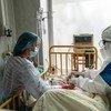 Una joven en una cama de hospital de Ucrania con COVID-19 es atendida por un doctor y su mamá.