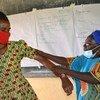 Une spécialiste traditionnelle des os examine une patiente en Ouganda.