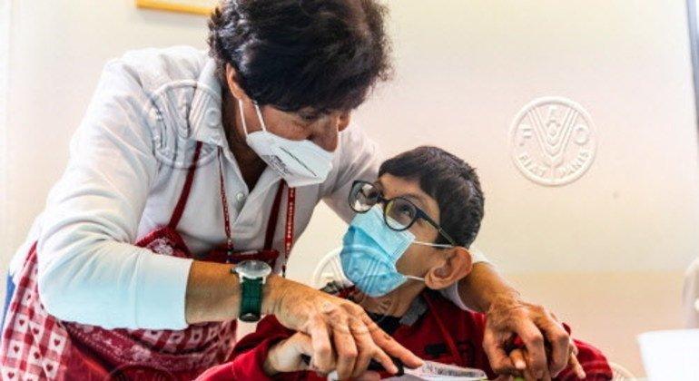روما ، إيطاليا - الطاهية ناهدة تساعد ريكاردو طفل وهو طفل من ذوي الاحتياجات الخاصة في تقطيع الخضار خلال فصل طبخ مع في كنيسة سانتا ماريا ريجينا باسيس.