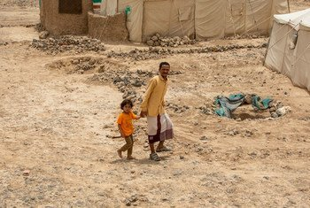 أب وطفله يسيران في مخيم للنازحين بالقرب من مدينة مأرب في اليمن.