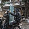 Two men transport glass panels via motor scooter in Vietnam. (file)