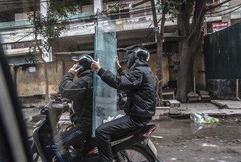越南两名男子通过小型摩托车运送玻璃面板。 (资料)