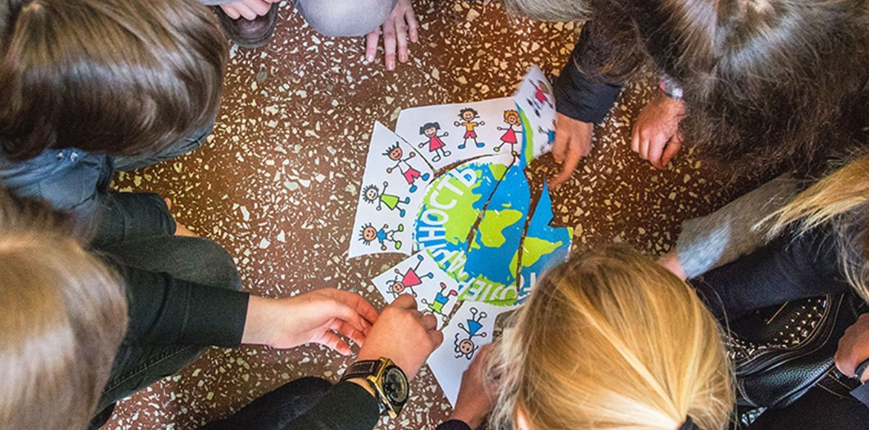 Niños en Ucrania juegan con un poster de los Objetivos de Desarrollo Sostenible que ilustran las diferentes razas alrededor del mundo.