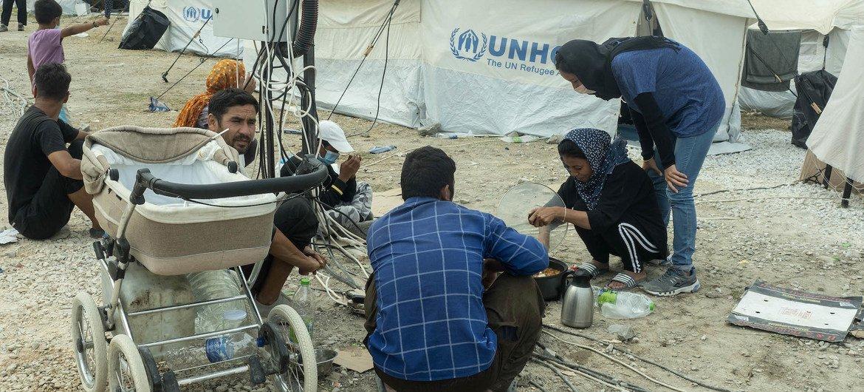 ग्रीस के लेसवॉस द्वीप स्थित मोरिया शिविर के आग में तबाह हो जाने के बाद, शरणार्थी एक अस्थाई स्थल पर खाना बकाते हुए और अपने मोबाइल चार्ज करते हुए.