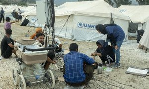 Refugees cook food and charge mobile phones at a temporary site after a fire destroyed the main camp at Moria, in Lesvos island, Greece.