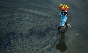 فتاة تحمل سلة من الفاكهة، تعبر شارعا غمرته المياه في مدينة كوتونو الساحلية في بنين.