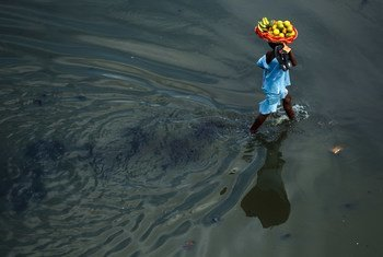 A girl carries a basket of fruits through a flooded street in Cotonou, a large port city in Benin.