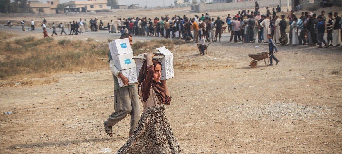 Trabajadores humanitarios distribuyendo asistencia de emergencia en la localidad de Ibrahim Khalil, Iraq.