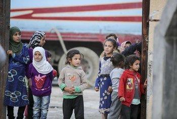 أطفال سوريون يقفون في ساحة مدرسة تحولت إلى مأوى مؤقت للاجئين في الرقة