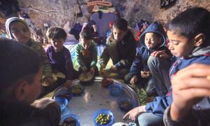 Des enfants déplacés partagent un repas dans une grotte souterraine où ils sont hébergés avec leurs familles dans le village de Taltouna, en Syrie.